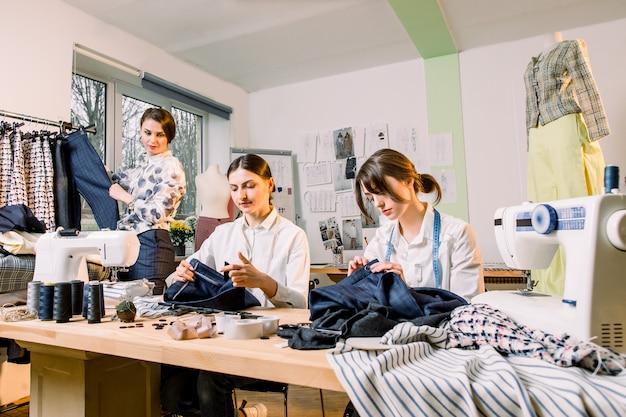 Vrouwelijke modeontwerper permanent in de buurt van kledingrek met modieuze stijlvolle handgemaakte kleding. twee jonge meisjes naaisters werken aan nieuwe broeken collectie voor klanten in gezellige workshop studio