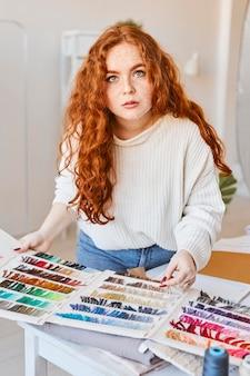 Vrouwelijke modeontwerper werken in atelier met kleurenpalet
