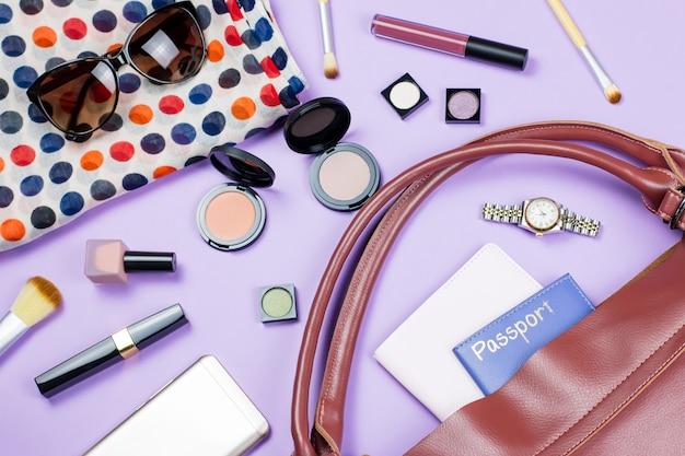 Vrouwelijke modetafel. make-up producten en vrouwenaccessoires liggen plat op een pasteltafel