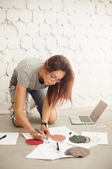 Vrouwelijke modevormgeving student tekening schetsen en illustraties werken op een laptop in een lichte studio-omgeving.