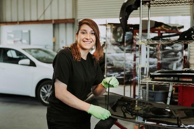 Vrouwelijke monteur die het weerzegel van een voertuig uittrekt