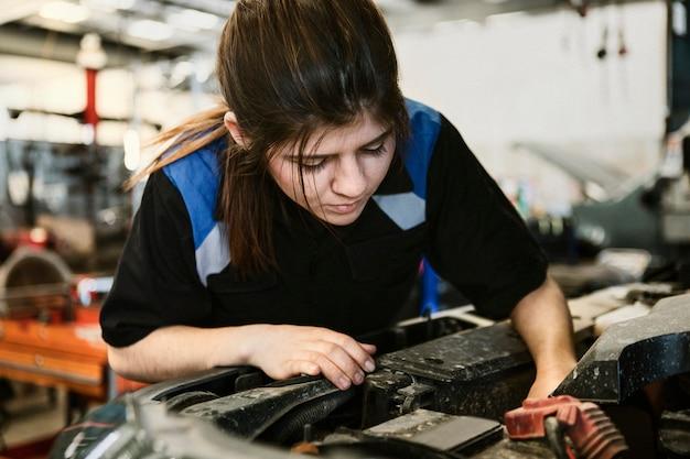 Vrouwelijke monteur die onder de motorkap van een auto controleert