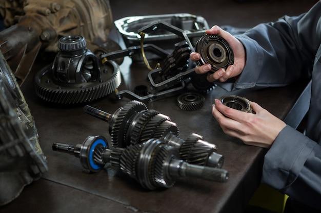 Vrouwelijke monteur die onderdelen van auto