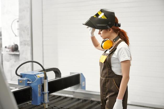 Vrouwelijke monteur in beschermend masker dat zich dichtbij cnc bevindt