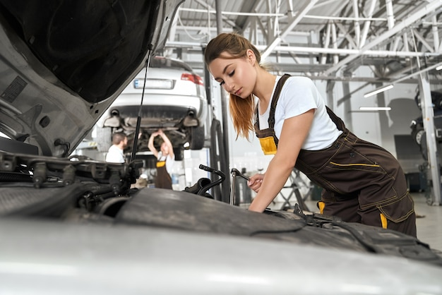 Vrouwelijke monteur in wit overhemd en overall repareren van motor