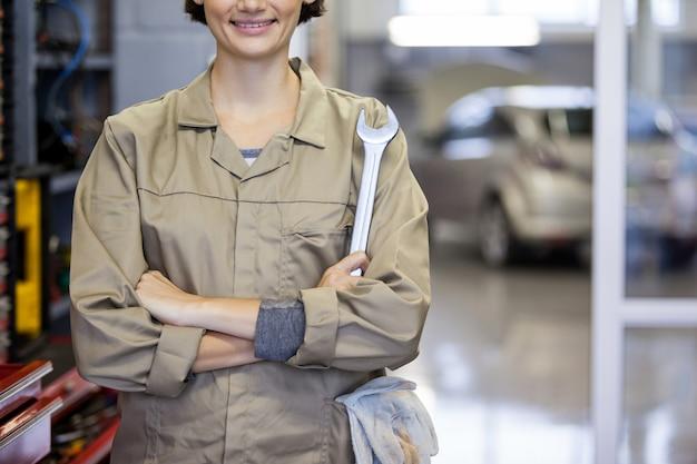 Vrouwelijke monteur met de armen gekruist en spanner