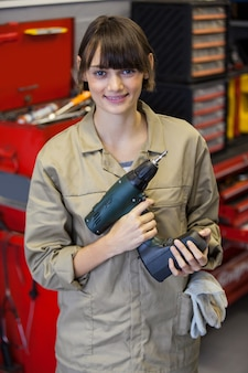 Vrouwelijke monteur met pneumatische moersleutel