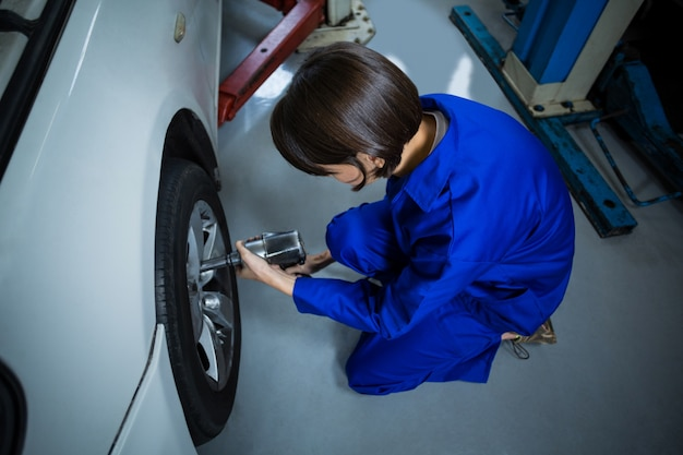 Vrouwelijke monteur tot vaststelling van een auto wiel met pneumatische moersleutel