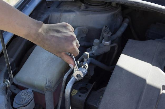 Vrouwelijke monteur voert reparaties uit onder de motorkap van een auto,