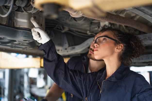 Vrouwelijke monteur wijst op het controleren van het onderhoud van een auto in de garage van de auto-service
