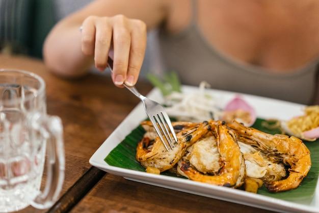 Vrouwelijke mooie hand met manicure houdt een vork boven garnalen met rijst en pittige saus.