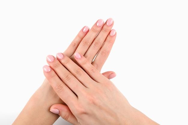 Vrouwelijke mooie handen met manicure op een afgelegen wit