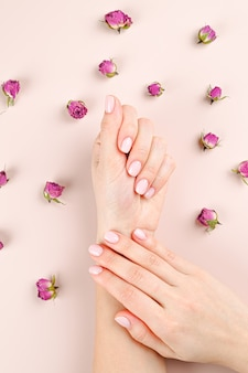 Vrouwelijke mooie handen op een achtergrond van rosebuds
