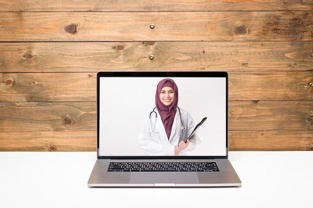 Vrouwelijke moslimarts die videogesprek voert op sociaal netwerk met patiëntadvies over gezondheidsproblemen.