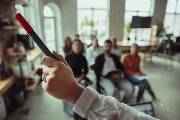 Vrouwelijke moslimspreker die presentatie geeft in zaal op workshop. publiek of conferentiezaal. close up van wijzende hand met marker. conferentie evenement, opleiding. onderwijs, diversiteit, inclusief concept.