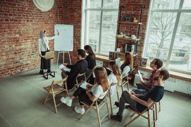 Vrouwelijke moslimspreker die presentatie geeft in zaal op workshop. publiek of zaal. hoge hoekmening van deelnemers in publiek. conferentie evenement, opleiding. onderwijs, diversiteit, inclusief concept.
