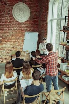 Vrouwelijke moslimspreker die presentatie in zaal geven op universitaire workshop
