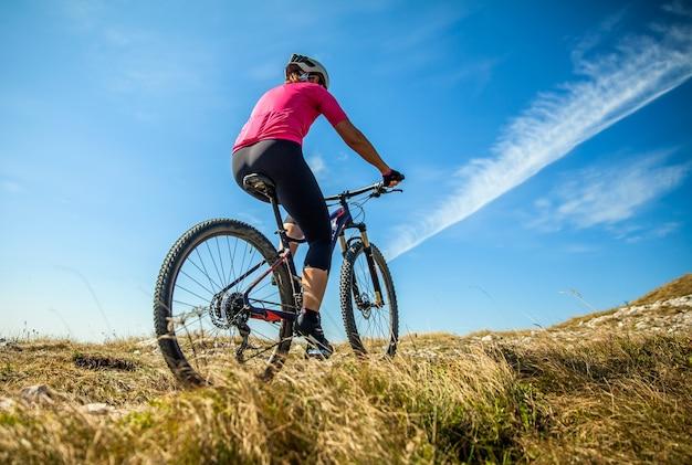 Vrouwelijke mountainbiker op nanos-plateau in slovenië op een zonnige dag