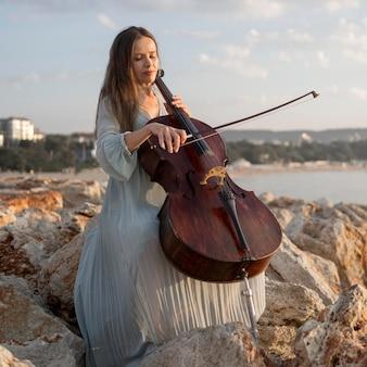 Vrouwelijke musicus die cello op rotsen speelt