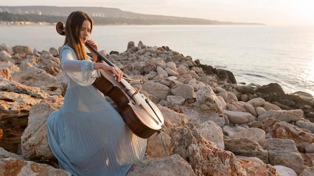 Vrouwelijke musicus die cello speelt bij zonsondergang met exemplaarruimte