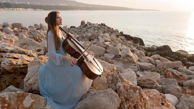 Vrouwelijke musicus die cello speelt bij zonsondergang