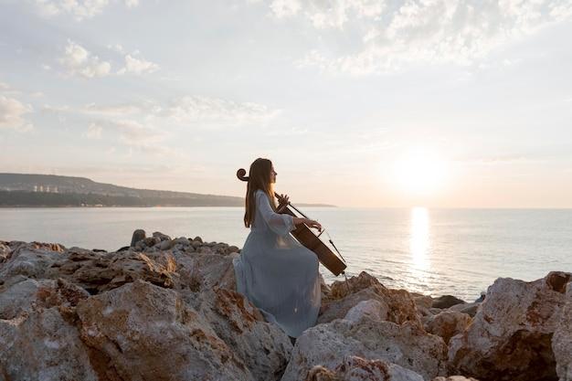 Vrouwelijke muzikant cello buiten spelen bij zonsondergang