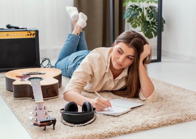 Vrouwelijke muzikant die thuis lied met hoofdtelefoons en akoestische gitaar schrijft