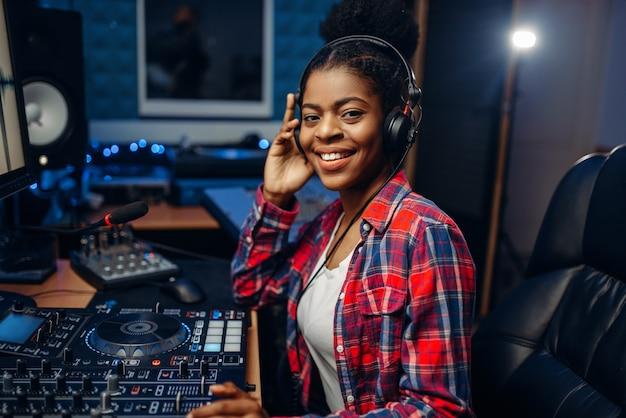 Vrouwelijke muzikant in koptelefoon in opnamestudio
