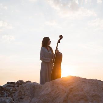 Vrouwelijke muzikant met cello buiten bij zonsondergang