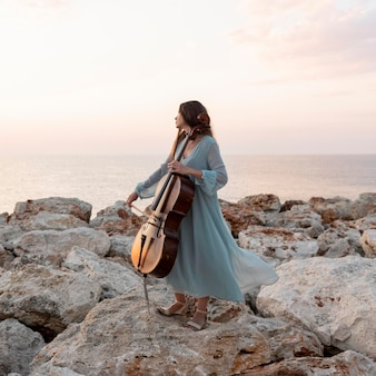 Vrouwelijke muzikant met cello buitenshuis