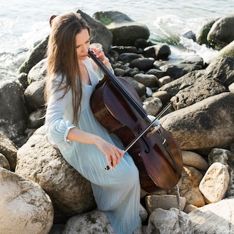 Vrouwelijke muzikant op rotsen die cello spelen door de zee