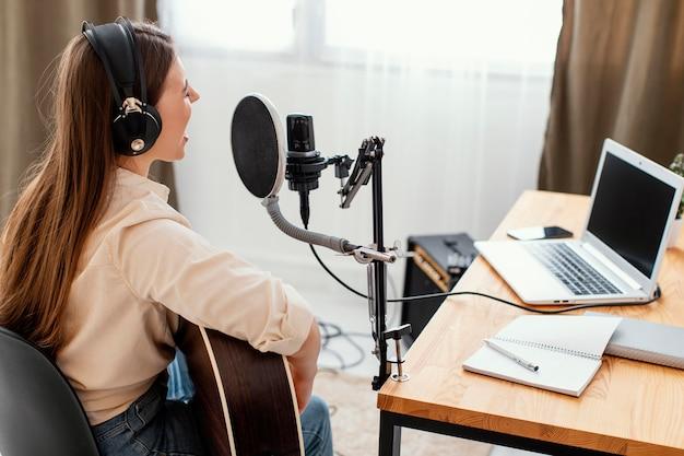 Vrouwelijke muzikant thuis lied opnemen en akoestische gitaar spelen