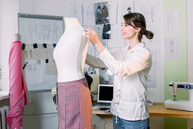 Vrouwelijke naaister die aan nieuw model maken broek op ledenpop in studio werken. fashion design mannequin meting concept.