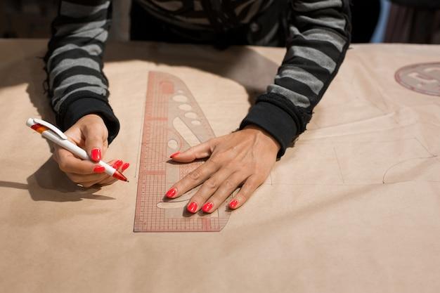Vrouwelijke naaister handen kleermaker tekenen op kraft papier voor het maken van patronen