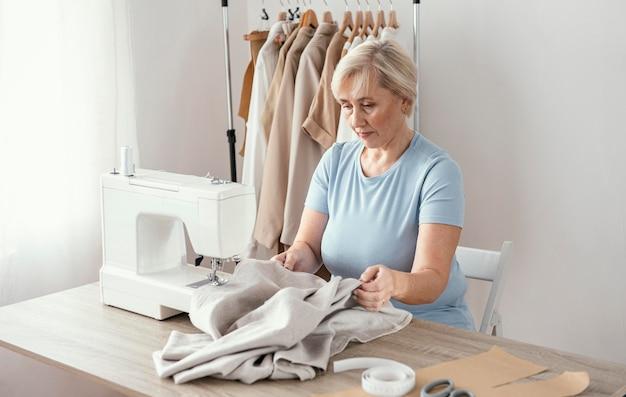 Vrouwelijke naaister in de studio met behulp van naaimachine