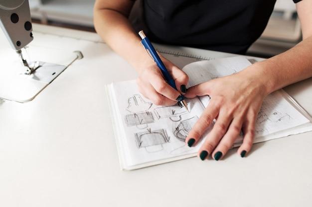 Vrouwelijke naaister tekening schets van tassen in atelier