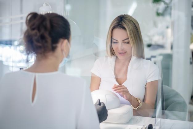 Vrouwelijke nagelkunstenaar die met de cliënt in een schoonheidssalon werkt