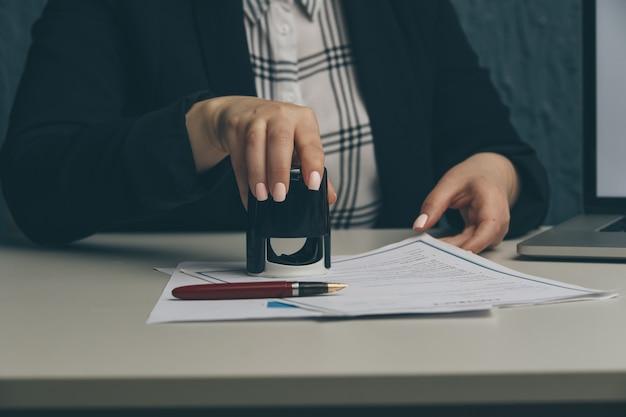 Vrouwelijke notaris stempelovereenkomst, bedrijfssecretaris, officieel document, geldigheid.