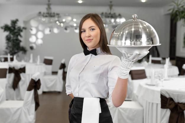 Vrouwelijke ober houdt een gesloten dienblad met een warme schotel vast.