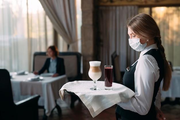 Vrouwelijke ober van europese verschijning in een medisch masker serveert latte-koffie.