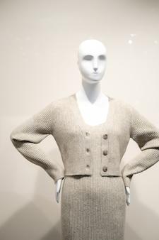 Vrouwelijke oefenpop in een grijze jurk en jas. kijk door het raam. mode concept