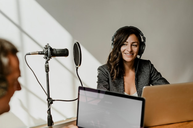Vrouwelijke omroep die haar gast interviewt in een studio