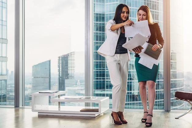Vrouwelijke onderneemsters die formele uitrusting dragen die documenten bespreken die zich in bureau gang bevinden.