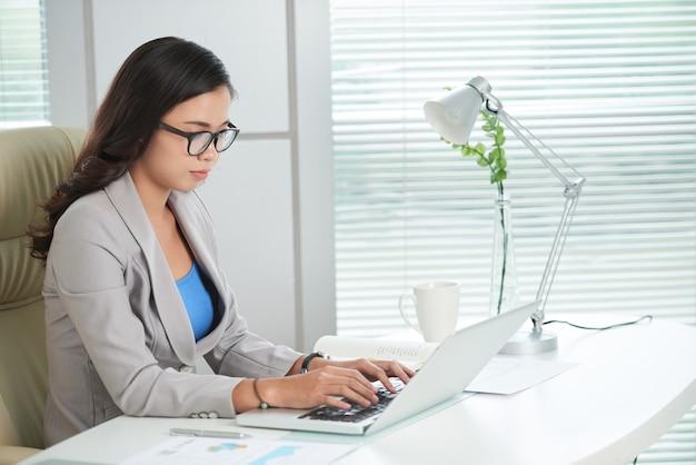 Vrouwelijke ondernemer die e-mails van collega's beantwoordt