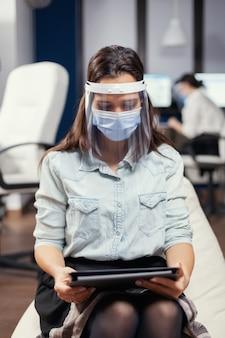 Vrouwelijke ondernemer die gezichtsmasker draagt tegen covid19 als veiligheidsmaatregel. multi-etnisch zakelijk team dat werkt met respect voor sociale afstand tijdens wereldwijde pandemie met covid-19.