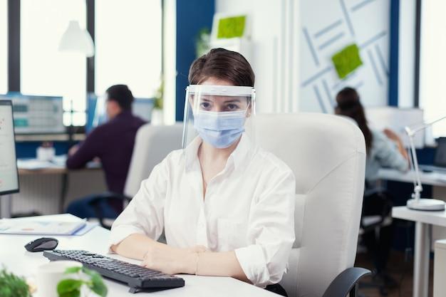 Vrouwelijke ondernemer die gezichtsmasker draagt tegen covid19 als veiligheidsmaatregel op de werkplek commercieel team dat werkt in een financieel bedrijf met respect voor sociale afstand tijdens wereldwijde pandemie.