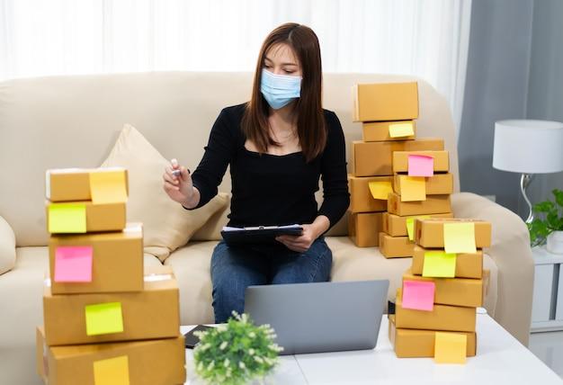 Vrouwelijke ondernemer die met laptop werkt en controleert om pakketdoos voor te bereiden voor levering aan klant thuiskantoor, hij draagt een gezichtsmasker ter bescherming van de coronavirus-pandemie