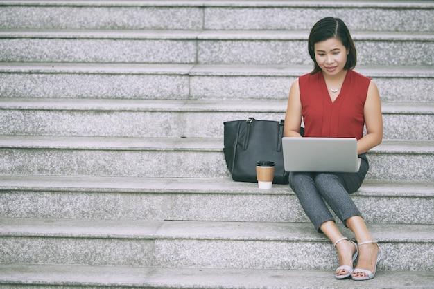 Vrouwelijke ondernemer die op laptop werkt