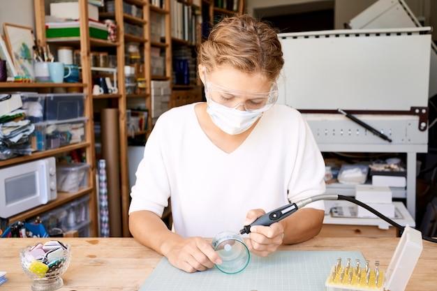 Vrouwelijke ondernemer in gezicht beschermend masker brandend glas in artisanale werkkamer