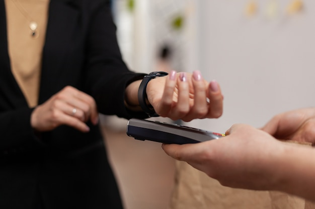 Vrouwelijke ondernemer in het bouwen van een kantoor met behulp van contactloze betaling van smartwatch voor voedselbezorging